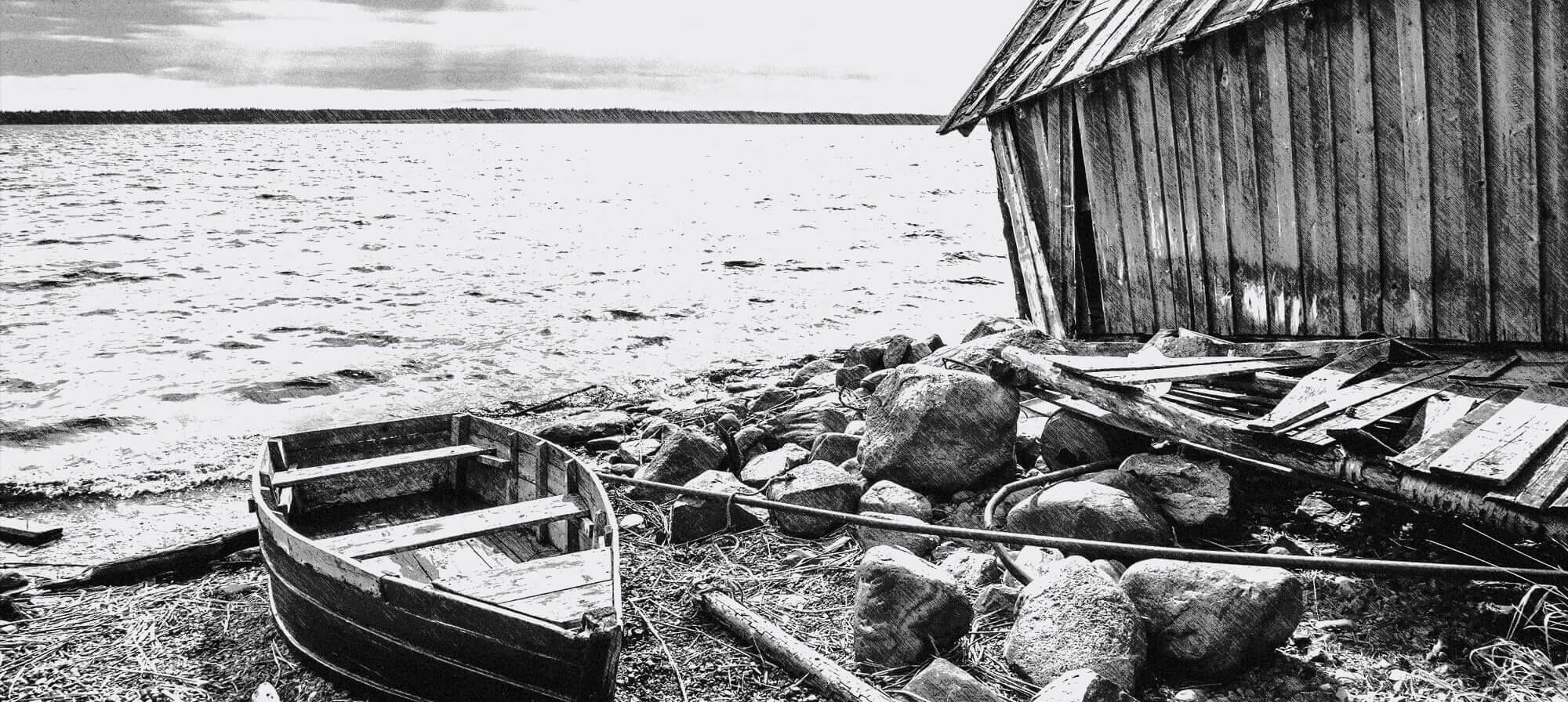 black and white photo of boat ashore near shack