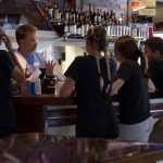 4 staff members standing at bar with bartender